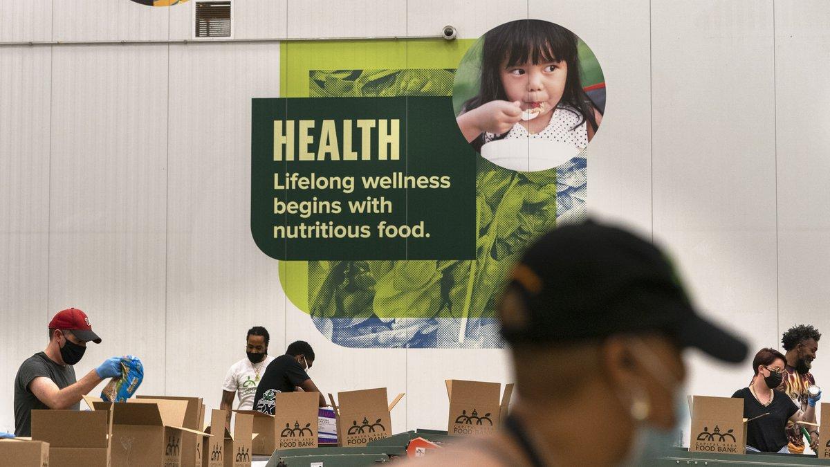 Los voluntarios empacan cajas de alimentos para su distribución en The Capital Area Food Bank,...