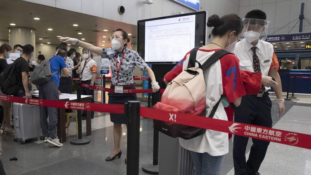 Airline employees redirect a traveler at a checkpoint for passengers from high risk areas to...
