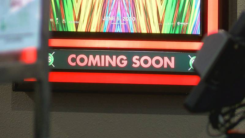 A sign previewing upcoming movies at Tyler's Times Square Grand Slam.